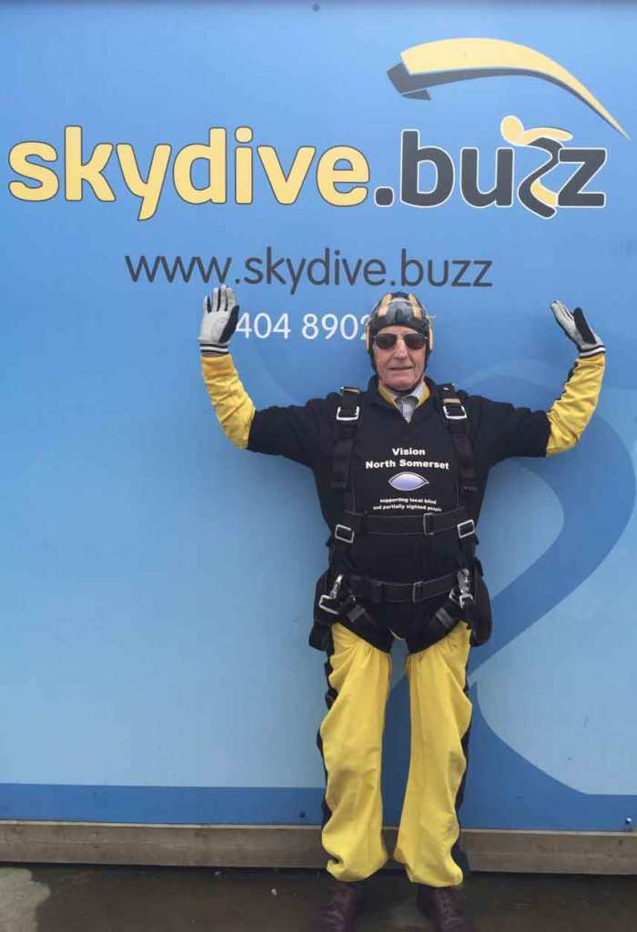 Photo of John celebrating in front of a Skydive Buzz sign.