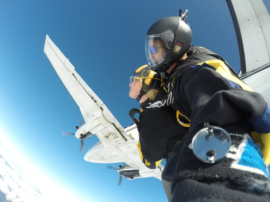 Image of Nina jumping out of a plane for her tandem skydive.